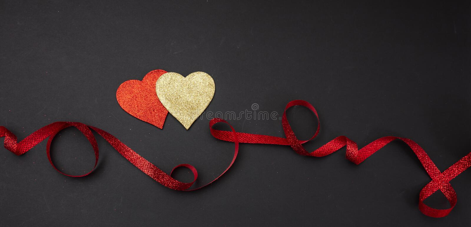 Top view of red and golden hearts with ribbon, black background, isolated, banner stock images