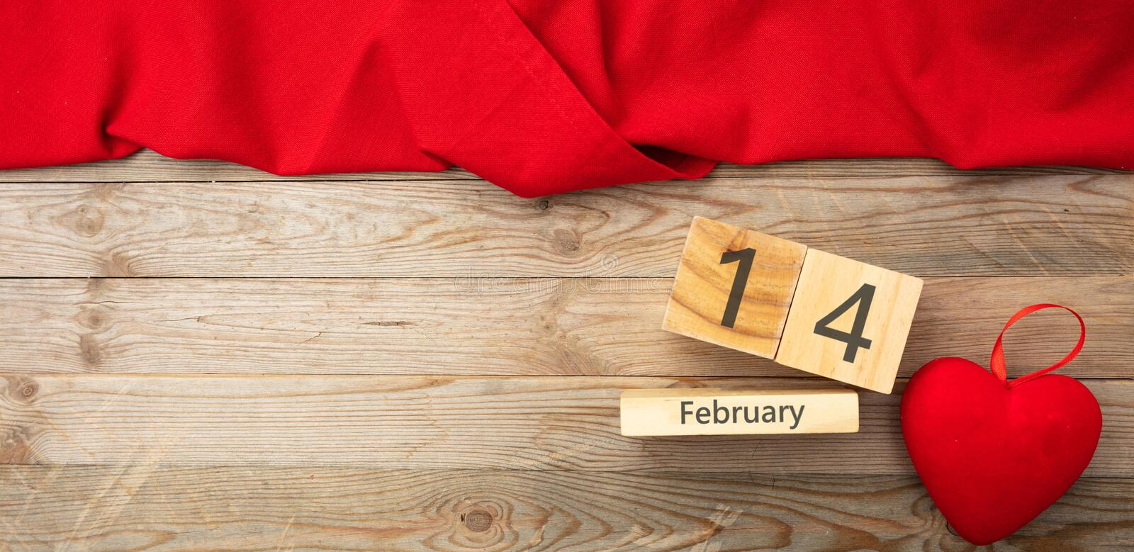 Valentines day. Top view of red heart and calendar date, wooden background stock image
