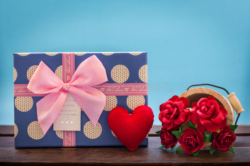 Valentines day vintage background with heart, red roses and gift. Box on wooden board stock image