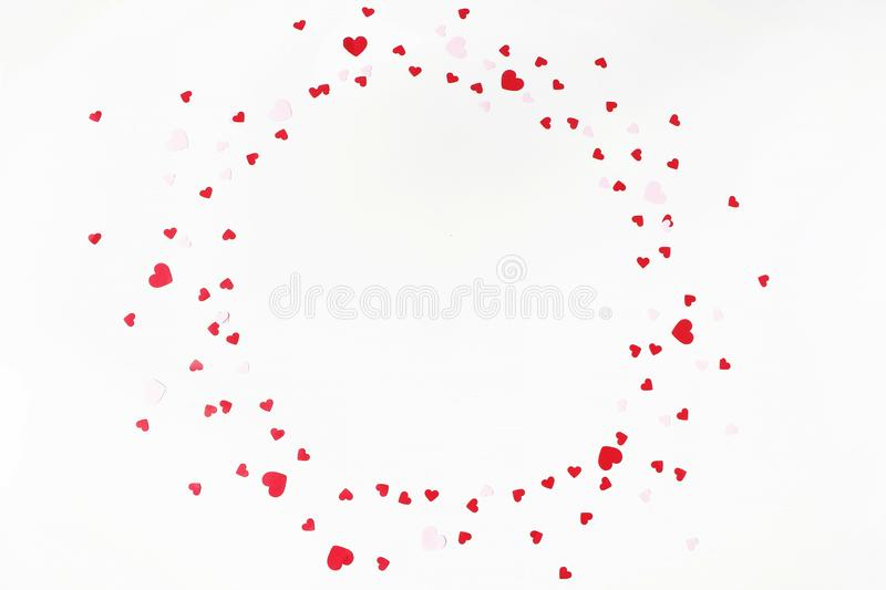 Valentines day or wedding festive composition. Circle made of red and pink paper heart shaped confetti isolated on white stock image