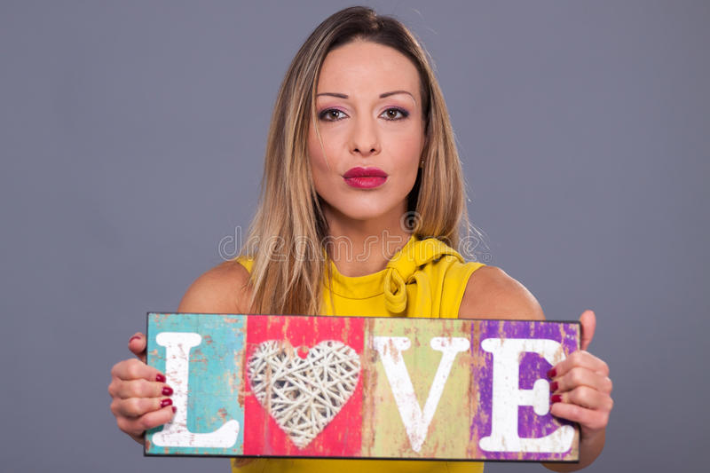 Valentines Day. Woman wearing yellow dress holding sign love symbol royalty free stock images