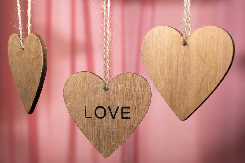 Valentines day wooden hearts with word love on pink background. Valentines day wooden hearts with the word love on a pink background royalty free stock image