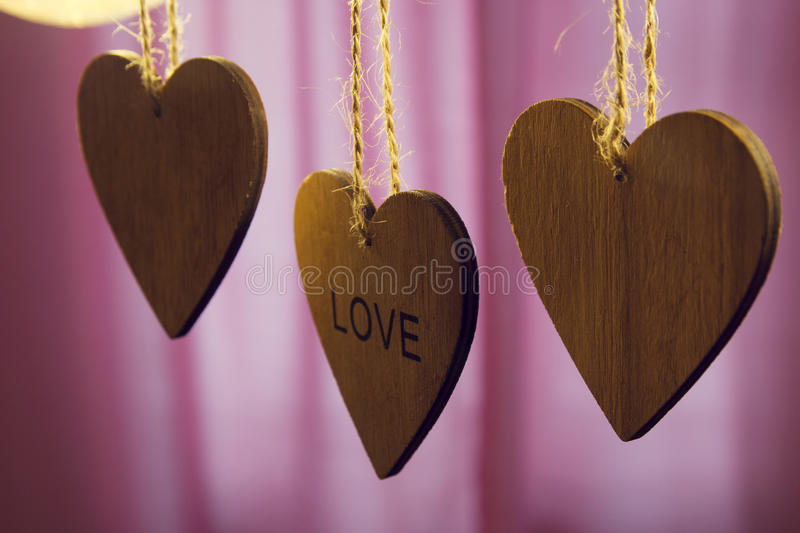 Valentines day wooden hearts with word love on pink background. Valentines day wooden hearts with the word love on a pink background royalty free stock photo