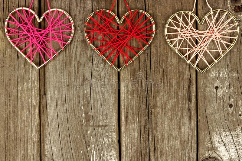 Valentines Day yarn hearts top border on rustic wood stock photos