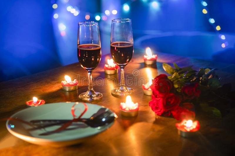 Valentines dinner romantic love concept Romantic table setting decorated with fork spoon on plate and couple champagne glass roses royalty free stock photos
