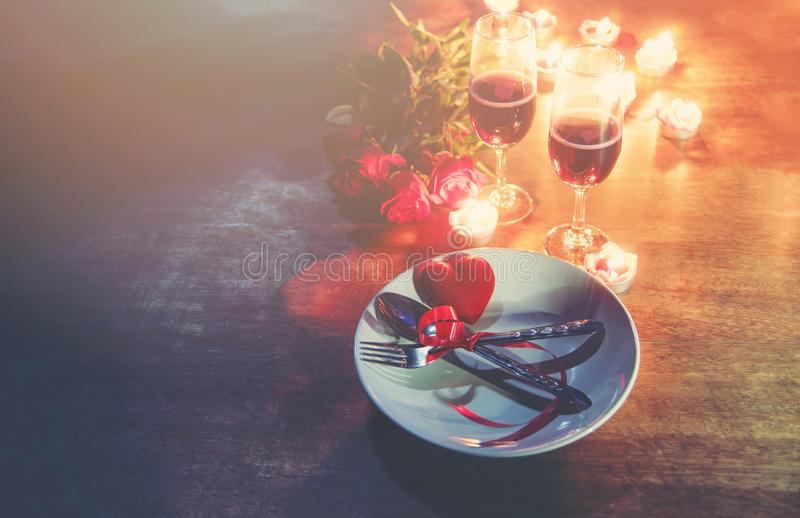 Valentines dinner romantic love concept Romantic table setting decorated with Red heart fork spoon on plate and couple champagne stock images