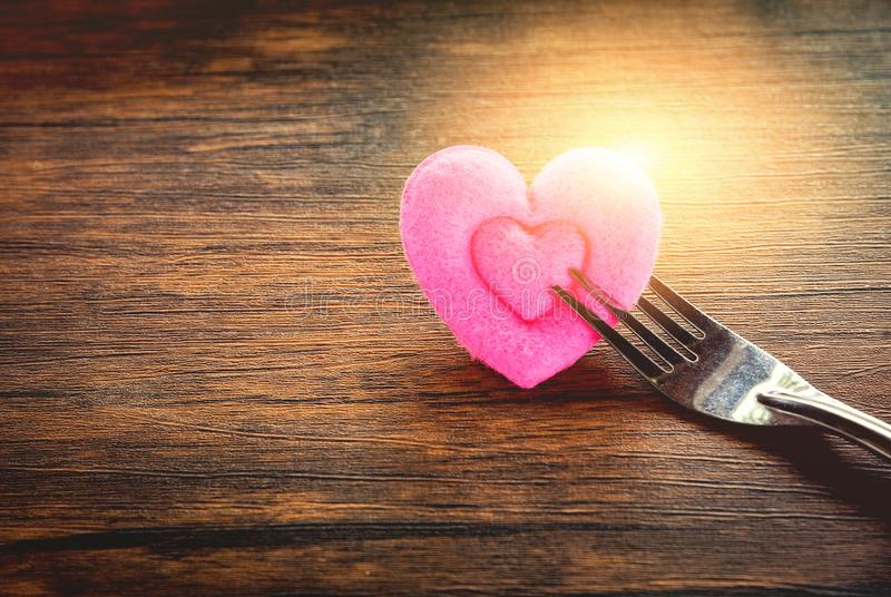 Valentines dinner romantic love food and love cooking concept - Romantic table setting decorated. With fork and pink heart on wooden rustic texture background royalty free stock photo