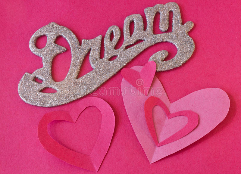 Valentines Dream. With the word Dream in glitter and cut our hearts on a red background royalty free stock photo