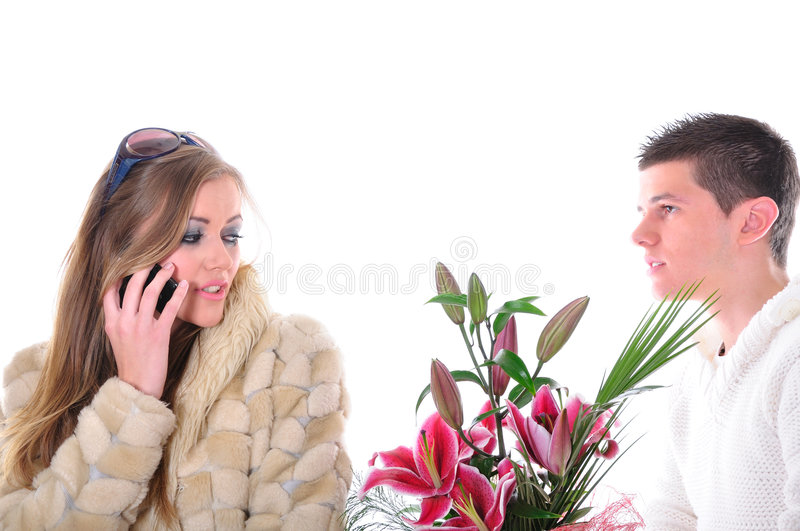 Valentines gone wrong. Heartbroken young man offering Valentines bouquet of flowers to a girl that ignores him royalty free stock images