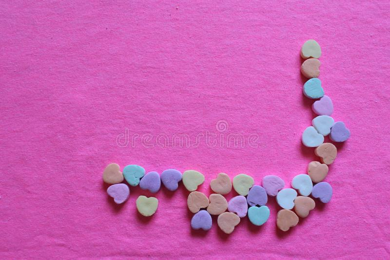 Valentines hearts highlighted bright pink hearts background. Valentine`s hearts with a highlighted bright pink background. Pastels accenting candy hearts royalty free stock photo