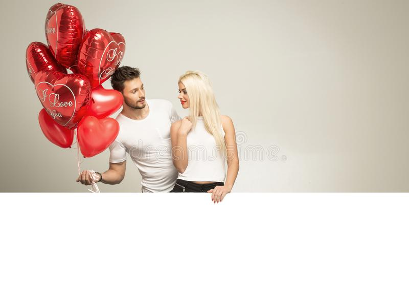 Valentines photo of young couple in love. With red balloons heart with white space for text, isolated on gray background royalty free stock photography