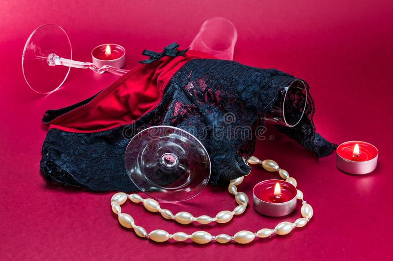 Valentines setup with erotic lingerie placed in between champagne glasses, pearl necklace and candles with a flame and fire. stock image
