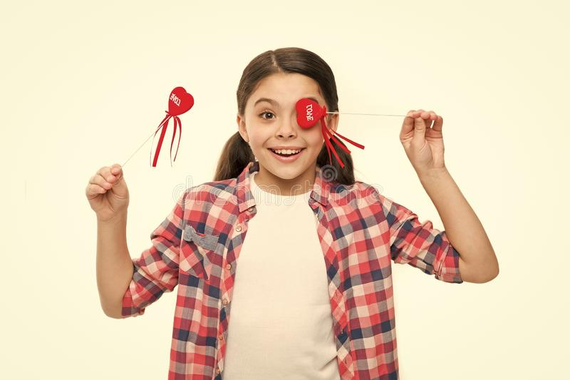 Valentines surprise. Funny small girl holding hearts on sticks. Cute girl with small red hearts. Small child with heart. Shaped decorations. Happy valentines royalty free stock photography