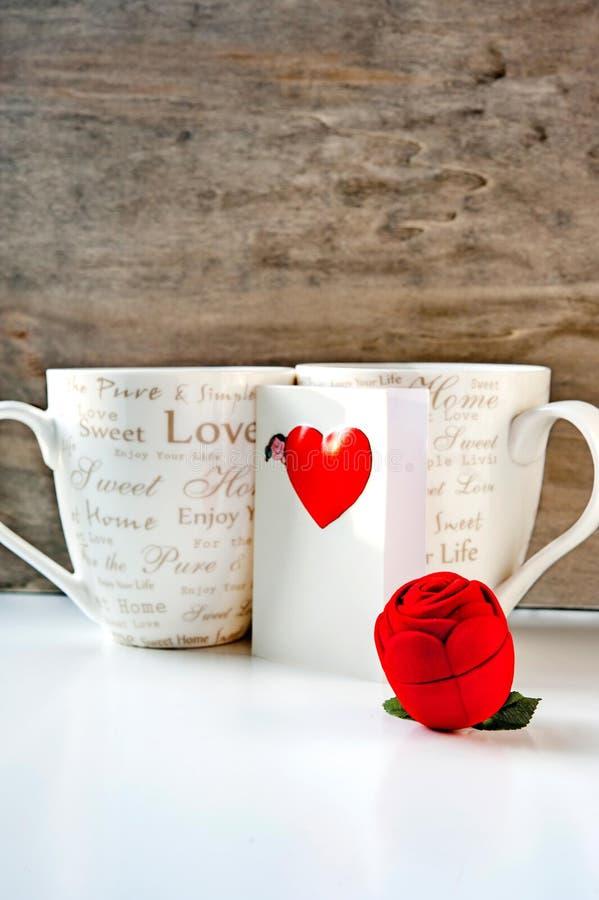 Valentingåva med förälskelsehälsningkortet och två kaffekoppar royaltyfri bild