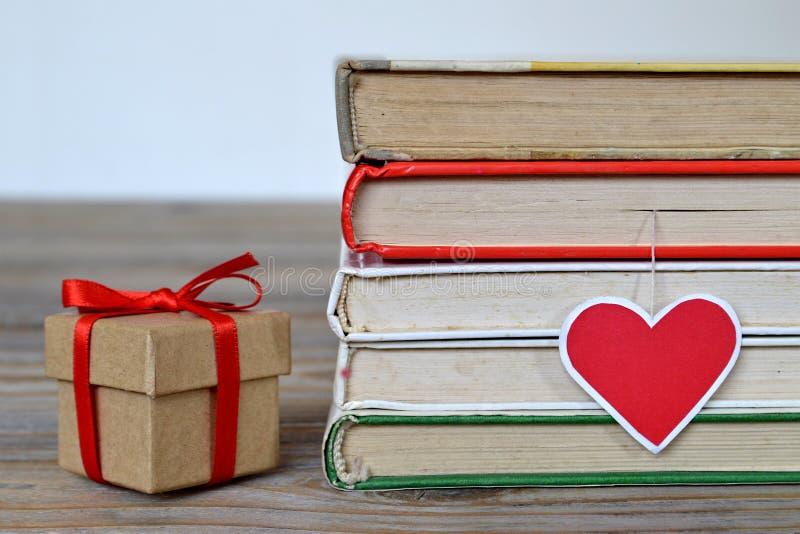 Valentingåvaask med det röda bandet och böcker arkivbild