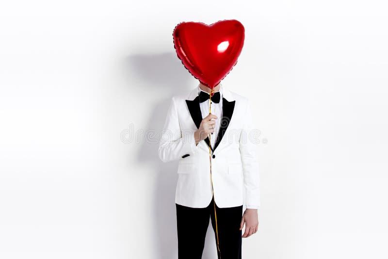 Valentinman Stilig pojkvän som rymmer den hjärta formade luftballongen Lycklig glad man Förälskelse lycklig s valentin för dag arkivbild