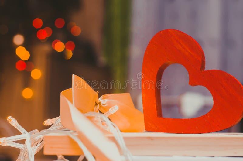 Valentinsgruß `s Tag ein hölzernes Herz mit einem gelben Bogen auf einem bokeh Hintergrund Das Konzept der Liebe Hintergrund bele stockfotografie