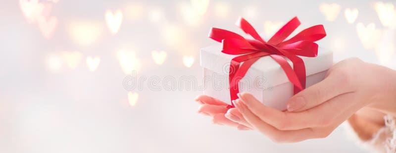 Valentinsgruß `s Tag Frau, die Geschenkbox mit rotem Bogen hält stockfotos