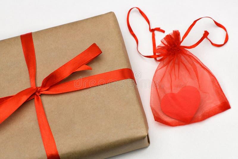 Valentinsgruß `s Tag Geschenkbox auf einem grauen Hintergrund in einem Kraftpapier-Braunpaket, das mit einem roten Band auf dem R lizenzfreies stockbild