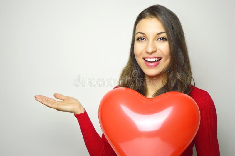 Valentinsgruß `s Tag Schöne junge Frau, die rotes Kleid trägt und einen roten Herzluftballon zeigt Ihr Produkt oder Text auf Whit stockfotos