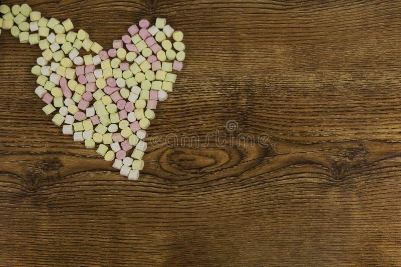 Valentinsgruß ` s Tag und Liebeskonzept auf hölzernem Hintergrund Süße Eibische gelegt in Herzform lizenzfreies stockfoto