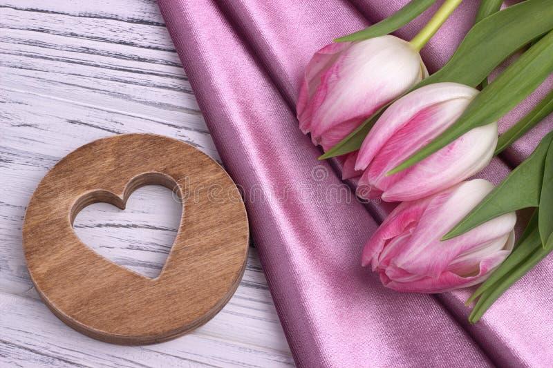 Valentinsgruß ` s Tageselegantes Stillleben mit rosafarbenem Gewebe der Tulpenblumen und Herz formen Zeichen lizenzfreie stockfotografie