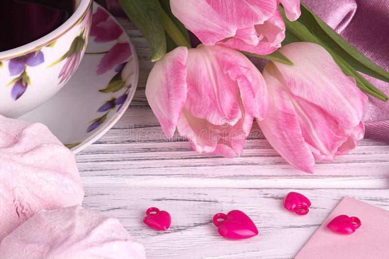 Valentinsgruß ` s Tageselegantes Stillleben mit Tulpe blüht Schale Herz-Formzeichens coffe Eibisches des roten auf weißem hölzern lizenzfreie stockfotografie