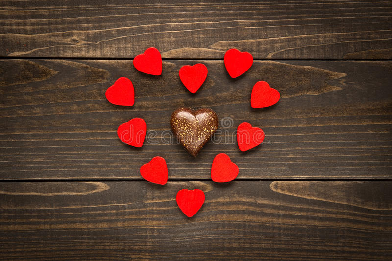 Valentinsgruß ` s Tageshintergrund Die roten Herzen, die in Herz gelegt werden, formen auf den hölzernen Schreibtisch lizenzfreies stockfoto