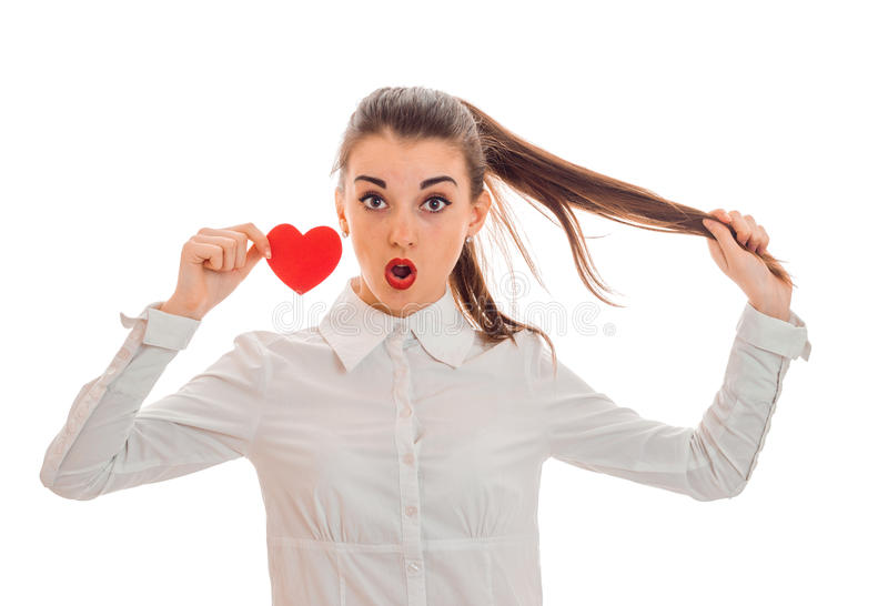 Valentinsgruß ` s Tageskonzept Liebe Junge überraschtes Mädchen mit dem roten Herzen lokalisiert auf weißem Hintergrund im Studio lizenzfreie stockbilder