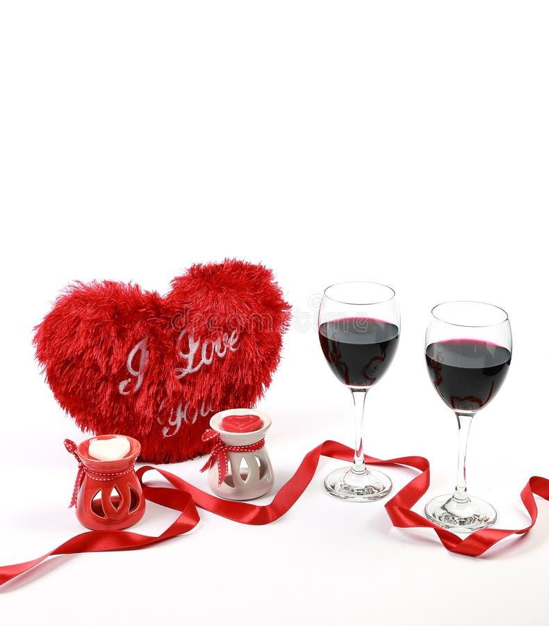 Valentinsgruß ` s Tageskonzept Zwei Gläser Rotwein mit Herzen formten Kerze und Kissen mit rotem Band auf lokalisiertem weißem Hi lizenzfreie stockbilder