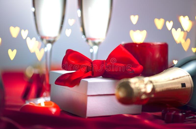 Valentinsgruß ` s Tagesromantisches Abendessen Champagne, Kerzen und Geschenkbox über Feiertagshintergrund lizenzfreies stockfoto