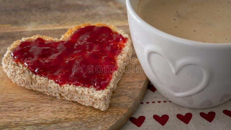 Valentinsgruß-Tagesfrühstück, Herz formte Toast mit Erdbeerstau und -kaffee lizenzfreie stockfotos