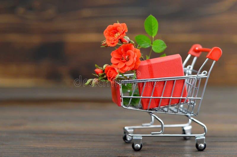 Valentinsgruß-Tagesgeschenkbox und rote Rosen im Warenkorb stockbild