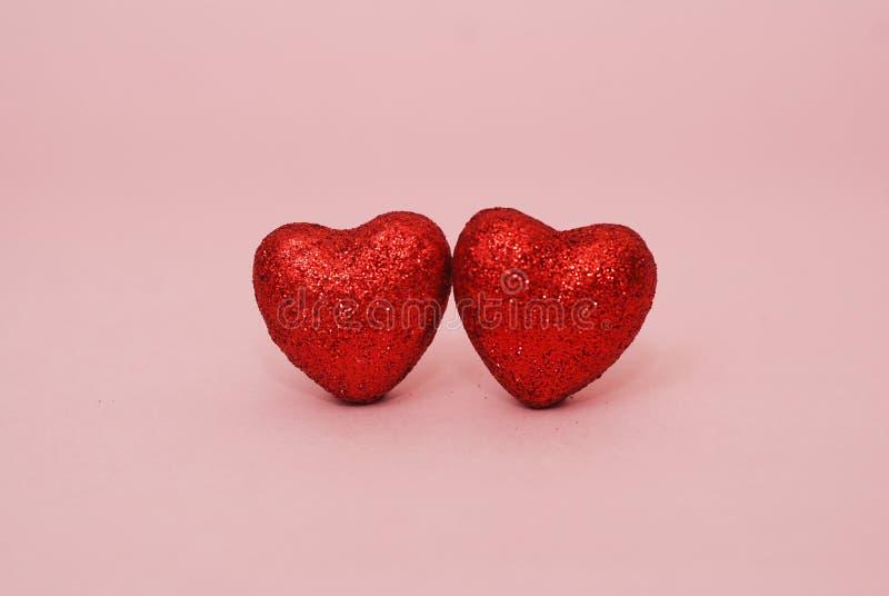 Valentinsgruß-Tagesherzen - zwei rote Herzen, Funkeln auf glänzendem, Schein auf rosa Hintergrund lizenzfreies stockbild