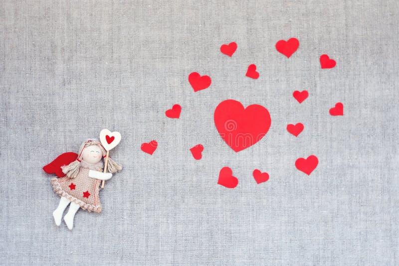 Valentinsgruß-Tageshintergrund mit Spielzeughandwerks-Engelsfee und viele roten Herzen bewölken Form auf Leinengewebe Valentine D stockfotos
