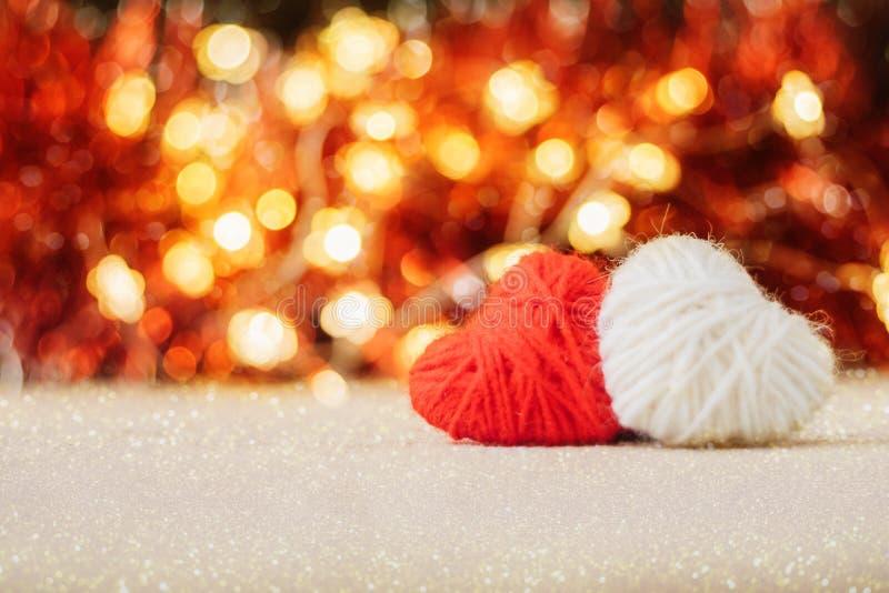 Valentinsgruß-Tageshintergrund mit zwei rot und weißes gestricktes flaumiges Herz auf rotes goldenes bokeh glänzendem Funkelnhint lizenzfreie stockfotografie