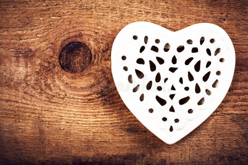 Valentinsgruß-Tageskarte mit weißem Lacy Heart auf hölzernem Hintergrund lizenzfreie stockfotografie