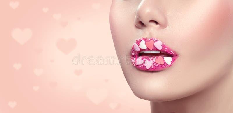 Valentinsgruß-Tagesmake-up Lippen mit rosa Herzzucker besprüht Valentinsgrußherz-Bonbonmake-up lizenzfreie stockfotos