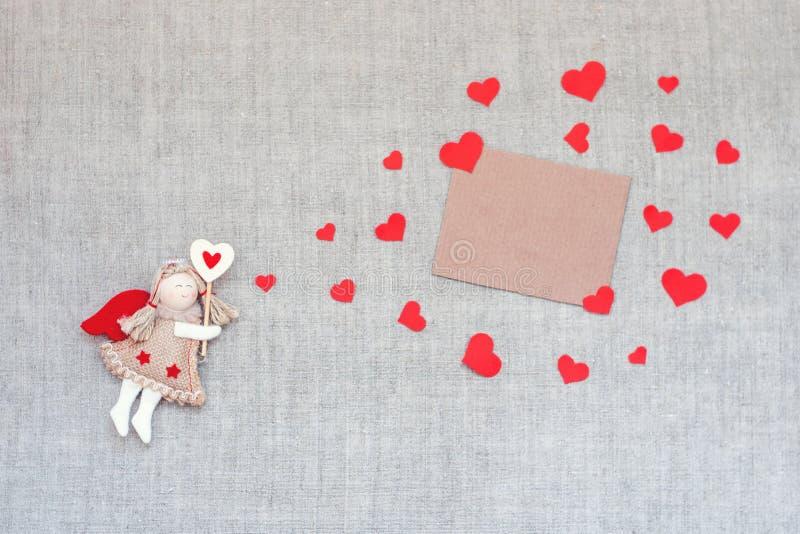 Valentinsgruß-Tagesmodell mit Spielzeughandwerks-Engelsfee, viele roten Herzen bewölken Form und leere Karte auf Leinengewebe Val lizenzfreie stockbilder