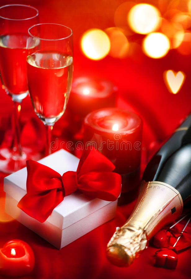 Valentinsgruß-Tagesromantisches Abendessen Champagne, Kerzen und Geschenkbox über Feiertagsrothintergrund stockbild