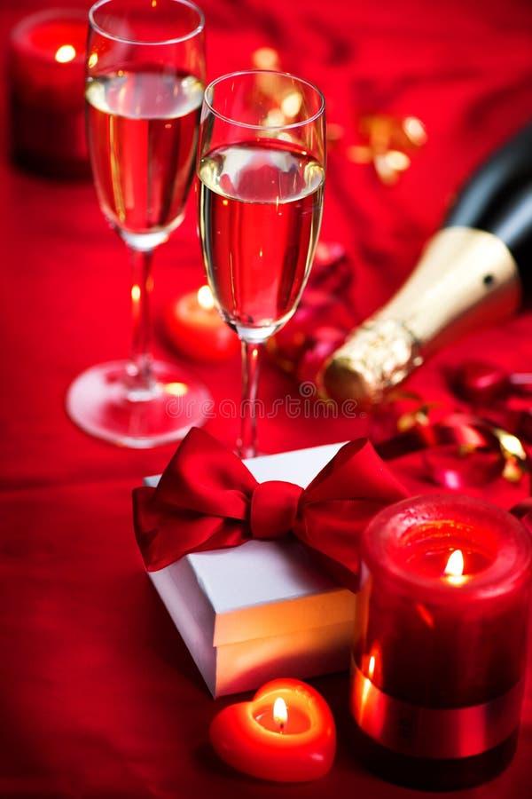 Valentinsgruß-Tagesromantisches Abendessen Champagne, Kerzen und Geschenkbox über Feiertagsrothintergrund stockfotos