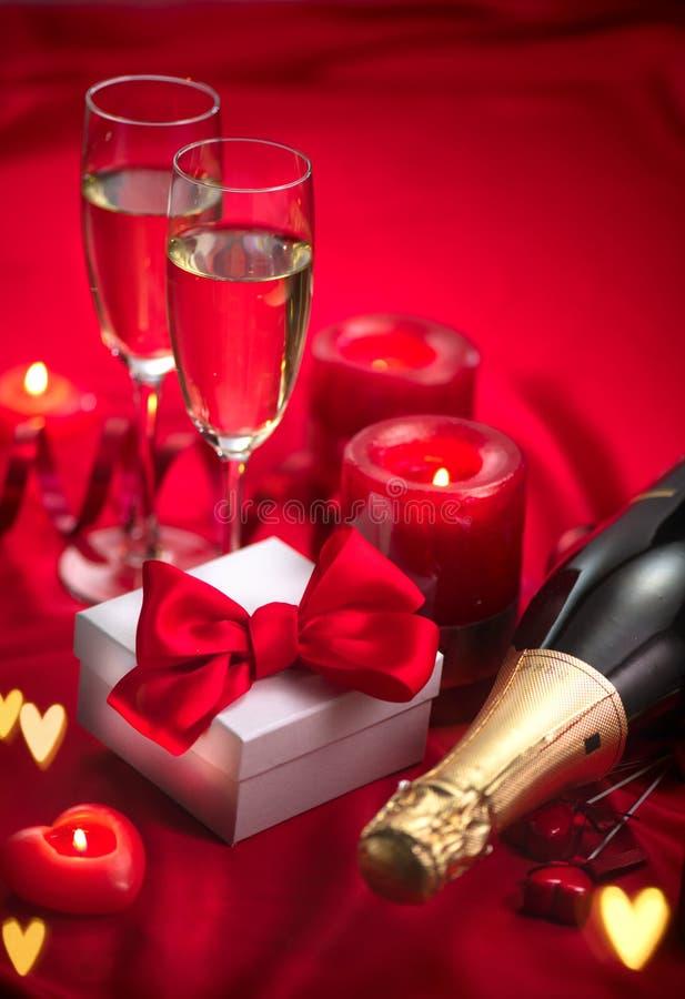 Valentinsgruß-Tagesromantisches Abendessen datum Champagne, Kerzen und Geschenkbox über Feiertagsrothintergrund stockfoto