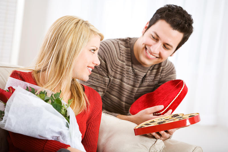 Valentinsgrußes: Frau erhält Süßigkeit und Blumen am Valentinstag stockbild