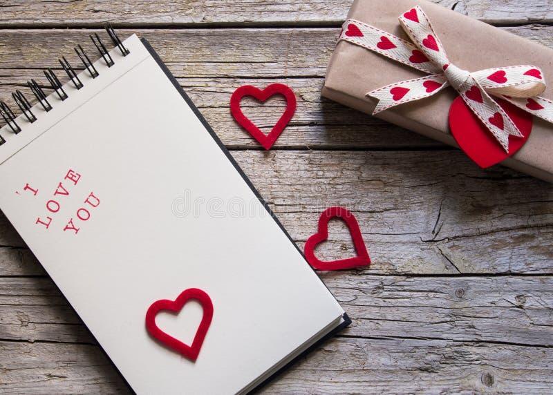Valentinsgrußgeschenkbox, Notizbuch und rote Herzform etikettieren auf hölzernem b stockfotografie