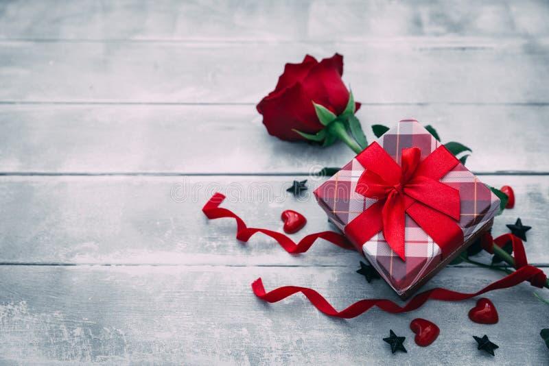 Valentinsgrußhintergrund mit Rotrosenblume und Mitbringselkasten auf rustikalem Holz stockfoto