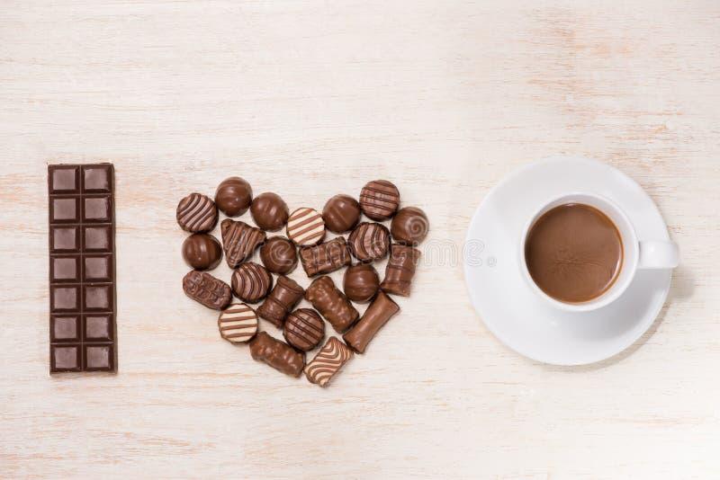 Valentinsgrußhintergrund mit Schokoladentrüffeln und Kaffeetasse lizenzfreie stockbilder
