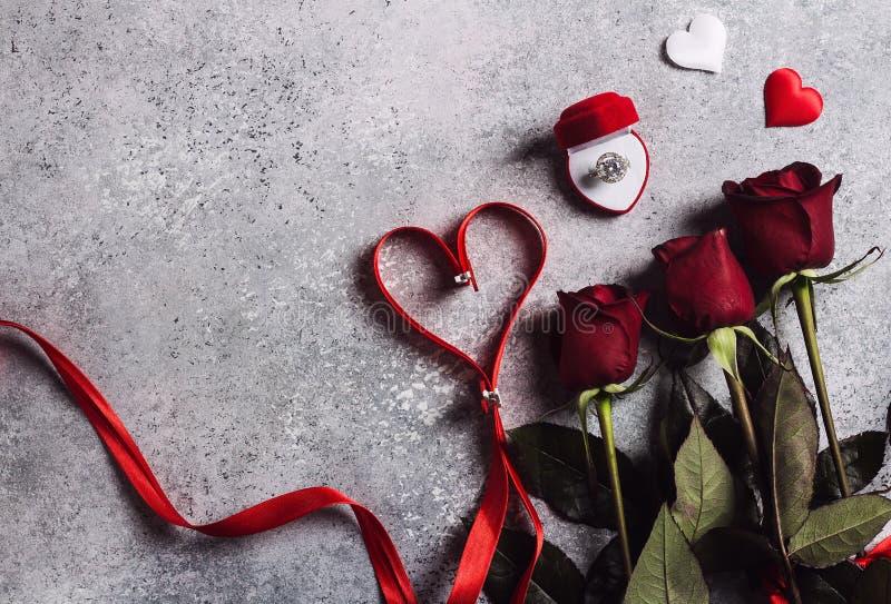 Valentinsgrußtag heiraten mich HochzeitsVerlobungsring im Kasten mit Blumenstrauß der roten Rosen und Bandherzen stockfotos