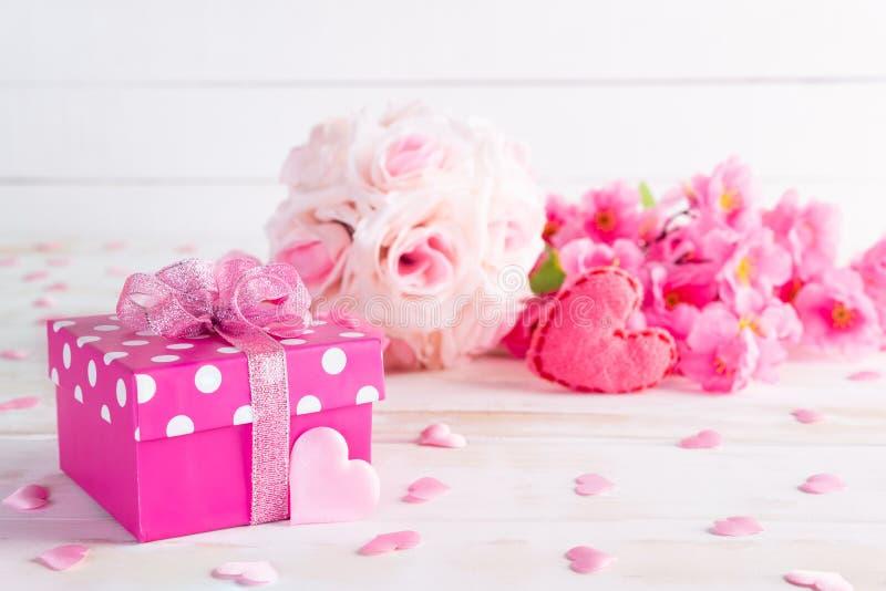 Valentinsgrußtag und Liebeskonzept Rosa Geschenkbox mit handgemachtem rotem Herzen und Blumen auf Holzklotz auf weißem hölzernem  stockbilder