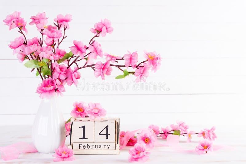 Valentinsgrußtag und Liebeskonzept Rosa Plum Peach Blossom im Vase mit am 14. Februar Text auf Holzklotzkalender auf weißem hölze lizenzfreies stockbild