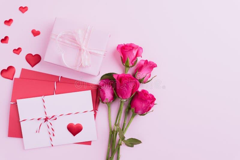 Valentinsgrußtag und Liebeskonzept Rosa Rosen, Geschenkbox mit rotem Herzen und rote rosa Buchstabeabdeckung auf rosa Hintergrund stockbilder